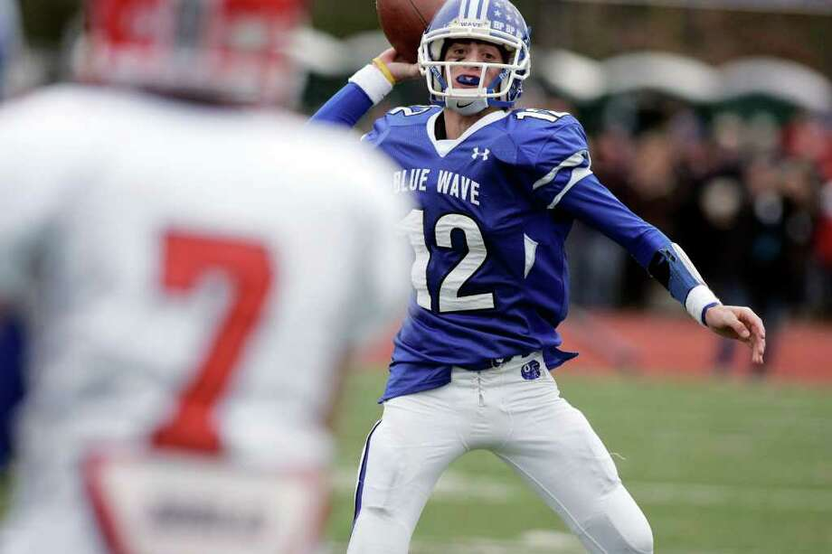Darien QB Chris Allam looks upfield for a open receiver during first half action against the visiting Rams of New Canaan. New Canaan manhandled the previous upbeaten Blue Wave easily. Photo: J. Gregory Raymond / © J. Gregory Raymond for Stamford Advocate Freelance