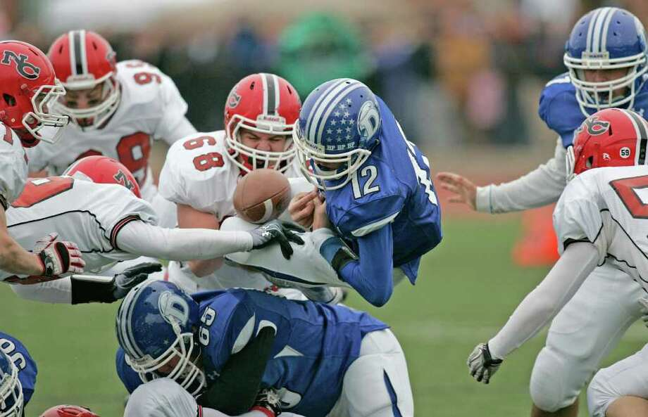 Chris Allam of Darien fumbles the football away in the Ram defensive zone as another Blue Wave drive stalled. The visiting Rams of New Canaan won the Turkey Day battle handily. Photo: J. Gregory Raymond / © J. Gregory Raymond for Stamford Advocate Freelance
