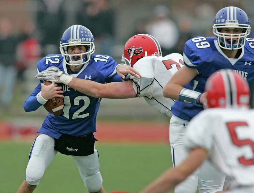 Darien QB Chris Allam is sacked by New Canaan's Jack Atchue during a Thanksgiving Day clash between the two towns. New Canaan won the game going away.