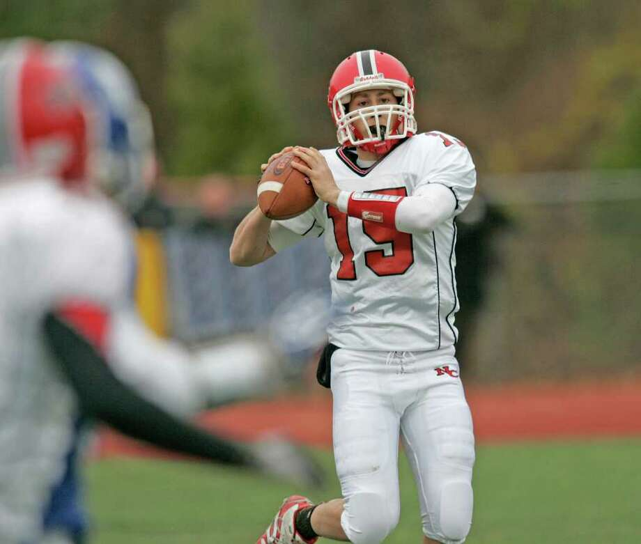 New Canaan QB Matthew Milano looks upfield for an open Ram receiver during third quarter action between New Canaan and Darien. Milano spearheaded a potent Ram offense as the Rams easily won the game against the previous unbeaten Blue Wave. Photo: J. Gregory Raymond / © J. Gregory Raymond for Stamford Advocate Freelance