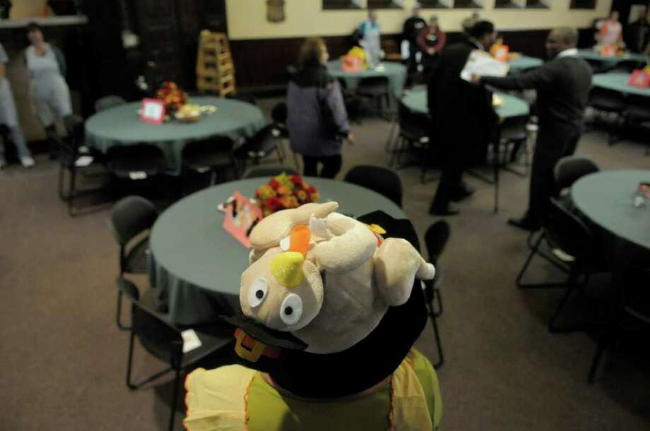 Volunteer Marji Knechtel, from Albany, wears her Thanksgiving hat as guests come in to take their seats at the start of the Annual Equinox Thanksgiving Day Community Dinner at the First Presbyterian Church in Albany, NY on Thursday, Nov. 25, 2010.  Hundreds of meals were served by volunteers at the church, and thousands of meals were also delivered to those in need who are home bound.   (Paul Buckowski / Times Union) Photo: Paul Buckowski / 00011174A