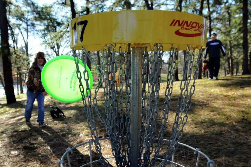 John Vendetti of Glenville, left, spins his disc toward the 17th basket on the disc golf course on Wednesday, Nov. 24, 2010, at Central Park in Schenectady, N.Y. At right is his brother Joe. (Cindy Schultz / Times Union)