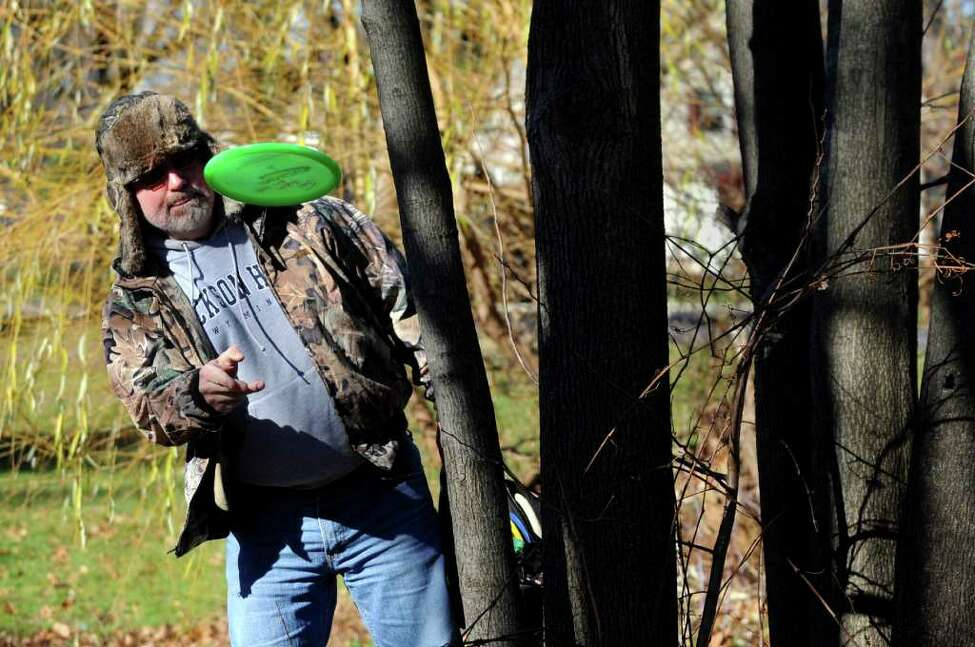 John Vendetti of Glenville has to avoid a natural obstacle on the disc golf course on Wednesday, Nov. 24, 2010, at Central Park in Schenectady, N.Y. At right is his brother Joe. (Cindy Schultz / Times Union)