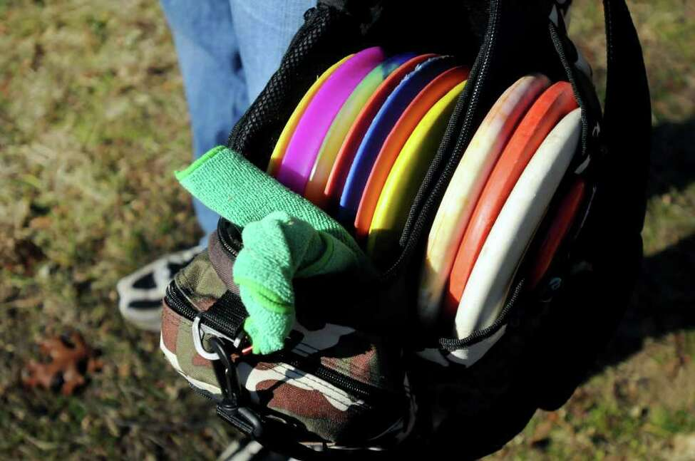 John Vendetti of Glenville has to carries his bag of discs to throw at different distances on the disc golf course on Wednesday, Nov. 24, 2010, at Central Park in Schenectady, N.Y. At right is his brother Joe. (Cindy Schultz / Times Union)