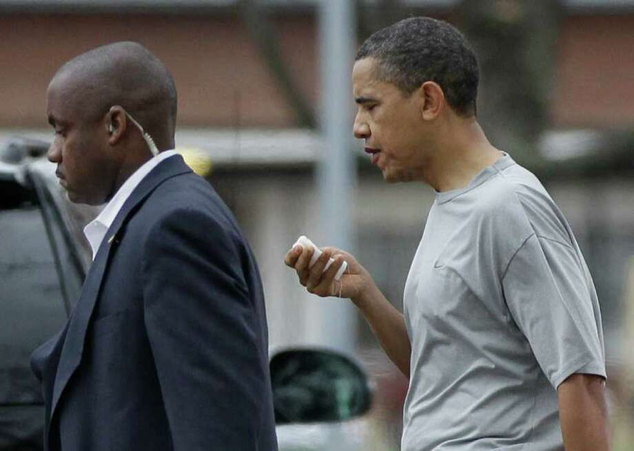 President Barack Obama walks with a U.S. Secret Service agent back to his vehicle after playing a private game of basketball at Fort McNair in Washington, Friday, Nov. 26, 2010. (AP Photo/Charles Dharapak) Photo: AP
