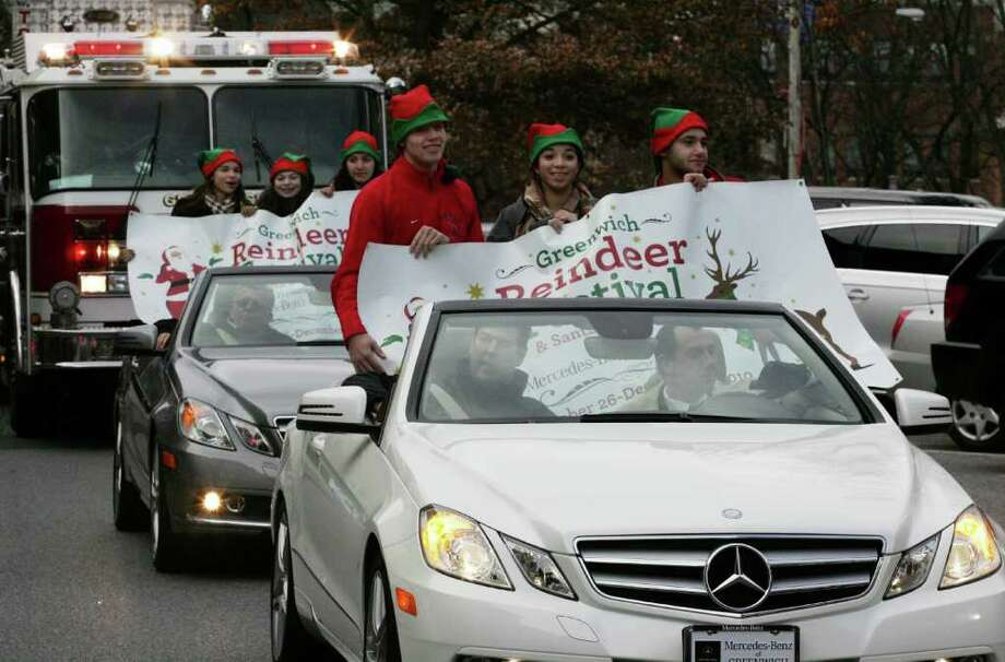 In back seat of front car, from left, Kids in Crisis Youth Corp members Eli Campbell, Nicole Gutierrez, and Mickey Smeriglio were driven down Greenwich Avenue by Mercedes-Benz of Greenwich employee Anthony Camardella, right, and Duncan Lee Friday afternoon Reindeer Festival parade which made its way from the First Presbyterian Church to McArdle's Florist & Garden Center on Arch Street, for the Greenwich Reindeer Festival. Photo: David Ames, David Ames/For Greenwich Time / Greenwich Time Freelance