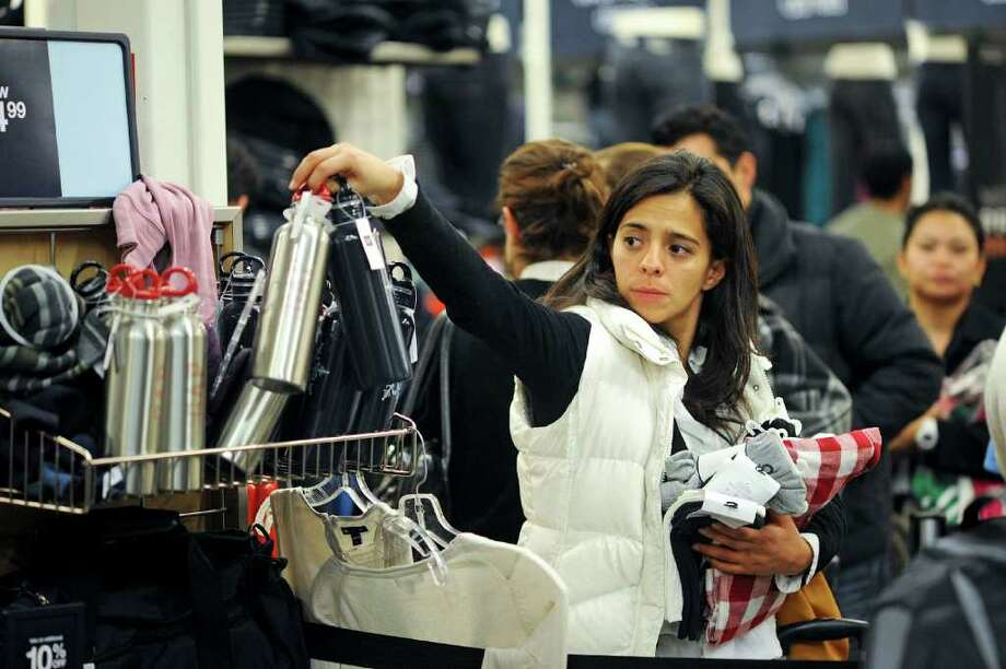 A woman grabs a water bottle for sale as she waits in line to purchase clothes at a Gap Inc. outlet store in the Las Americas Premium Outlets mall in San Diego, California, U.S., on Friday, Nov. 26, 2010. Shoppers on Black Friday, the biggest shopping day of the year, are taking advantage of deals as they face down a slower economic recovery than projected. Photographer: David Maung/Bloomberg Photo: David Maung, Bloomberg