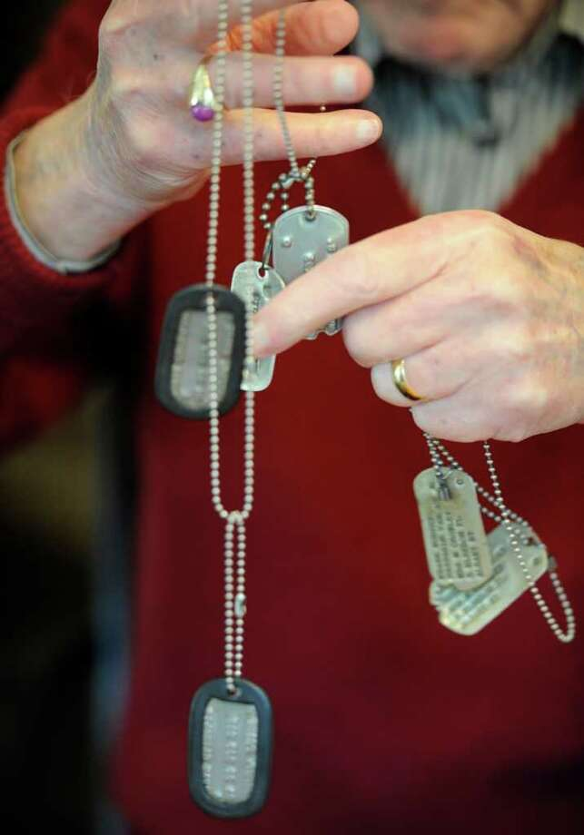 Frank Murphy shows the dog tags from the three wars in which he saw combat: World War II, Korea and Vietnam. (Skip Dickstein/Times Union) Photo: Skip Dickstein
