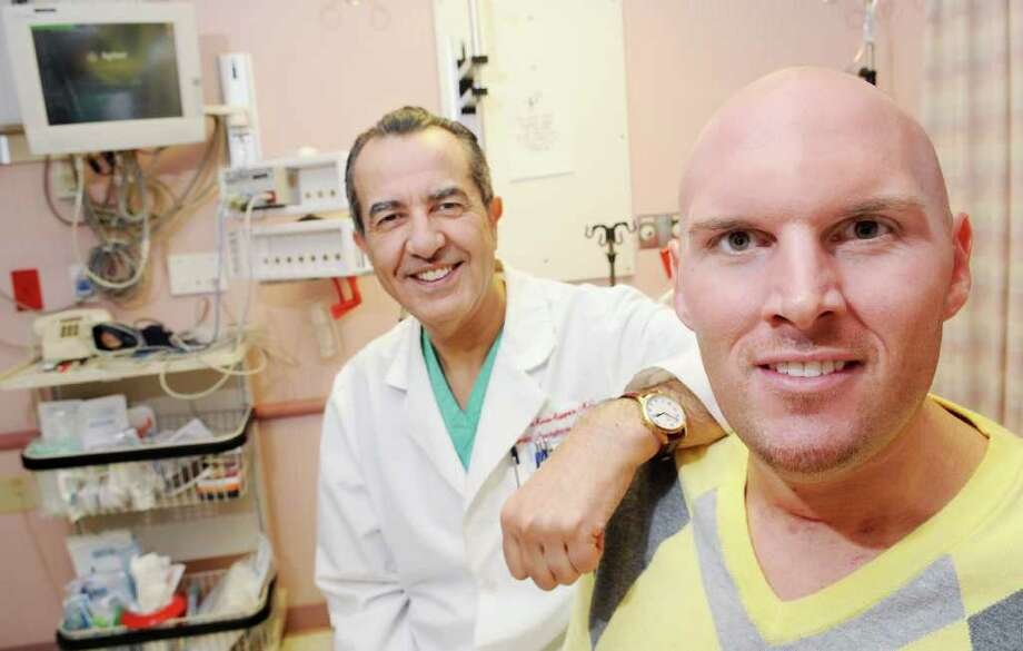 "Left to right: Cardiologist Dr. Guillermo Sosa-Suarez, on staff at St. Peter's Hospital, with his miracle patient Robert Schmit, who, weeks ago, suffered a cardiac arrest while working out at a health club with his girlfriend and subsequently slipped into a coma.  Without the ""Perfect Storm"" of quick acting medical professional, including  the CPR intervention of Schmit's girlfriend, Julia Palma, who happens to be an RN, the St. Peter's Hospital Cardiac Cath Lab, the use of a therapeutic hypothermia blanket, and the innovative work of  Dr. Guillermo Sosa-Suarez, it is believed that Schmit would have died.  While in the coma it was for a time thought that the 27 year old was brain dead.  Now discharged from the hospital, the happy ending is that he seems to have no mental impairment, and a new lease on life. ?The dr. and patient and other hospital staff had a reunion in the Cardiac Wing of St. Peter's  in Albany, NY, on Monday, Nov. 15, 2010, when Schmit and his family came for a visit after some followup medical appointments.  Photos for upcoming medical story by Cathleen Crowley, and for a Web Gallery.    (Luanne M. Ferris / Times Union ) Photo: Luanne M. Ferris"