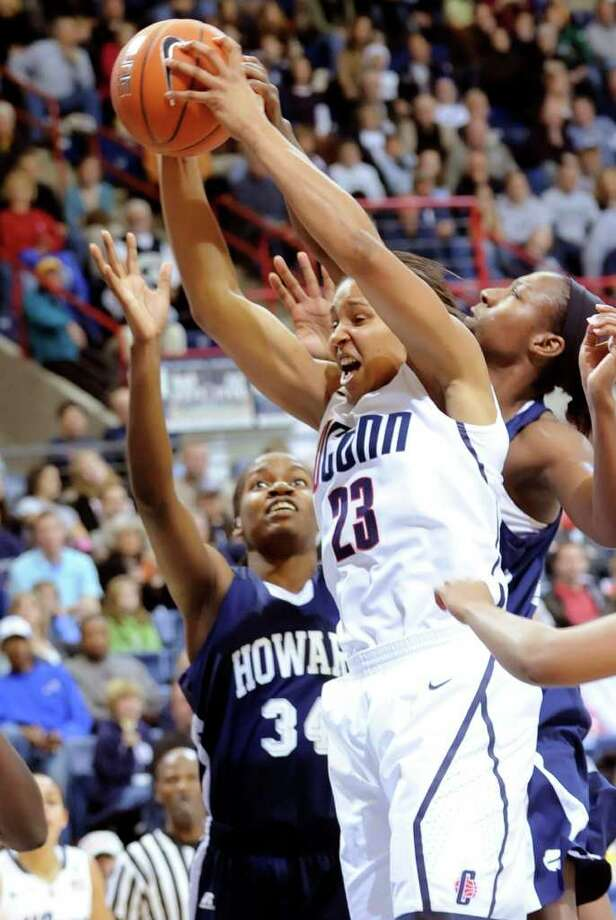 Connecticut's Maya Moore pulls in a rebound as Howard's Portia Deterville, left, and Jerelle Gorham, right, defend in the first half of an NCAA women's college basketball game at Storrs, Conn., Friday, Nov. 26, 2010. No. 1 UConn defeated Howard 86-25. Connecticut set the women's record for consecutive victories with its 82nd in a row. (AP Photo/Bob Child) Photo: Bob Child, ASSOCIATED PRESS / FRE 170410 AP