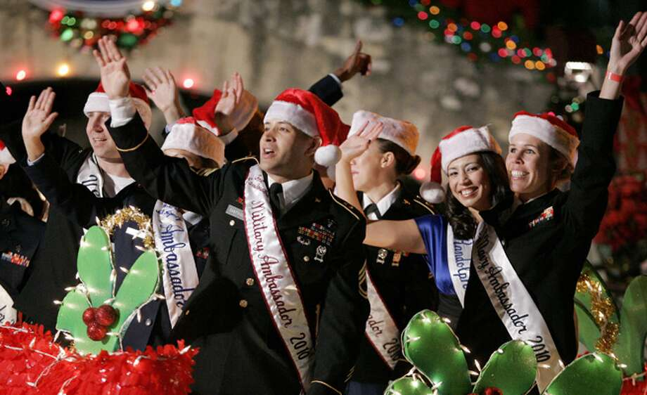 Members of the Joint Base San Antonio Military Ambassadors wave to spectators during the 2010 Ford Holiday River Parade.