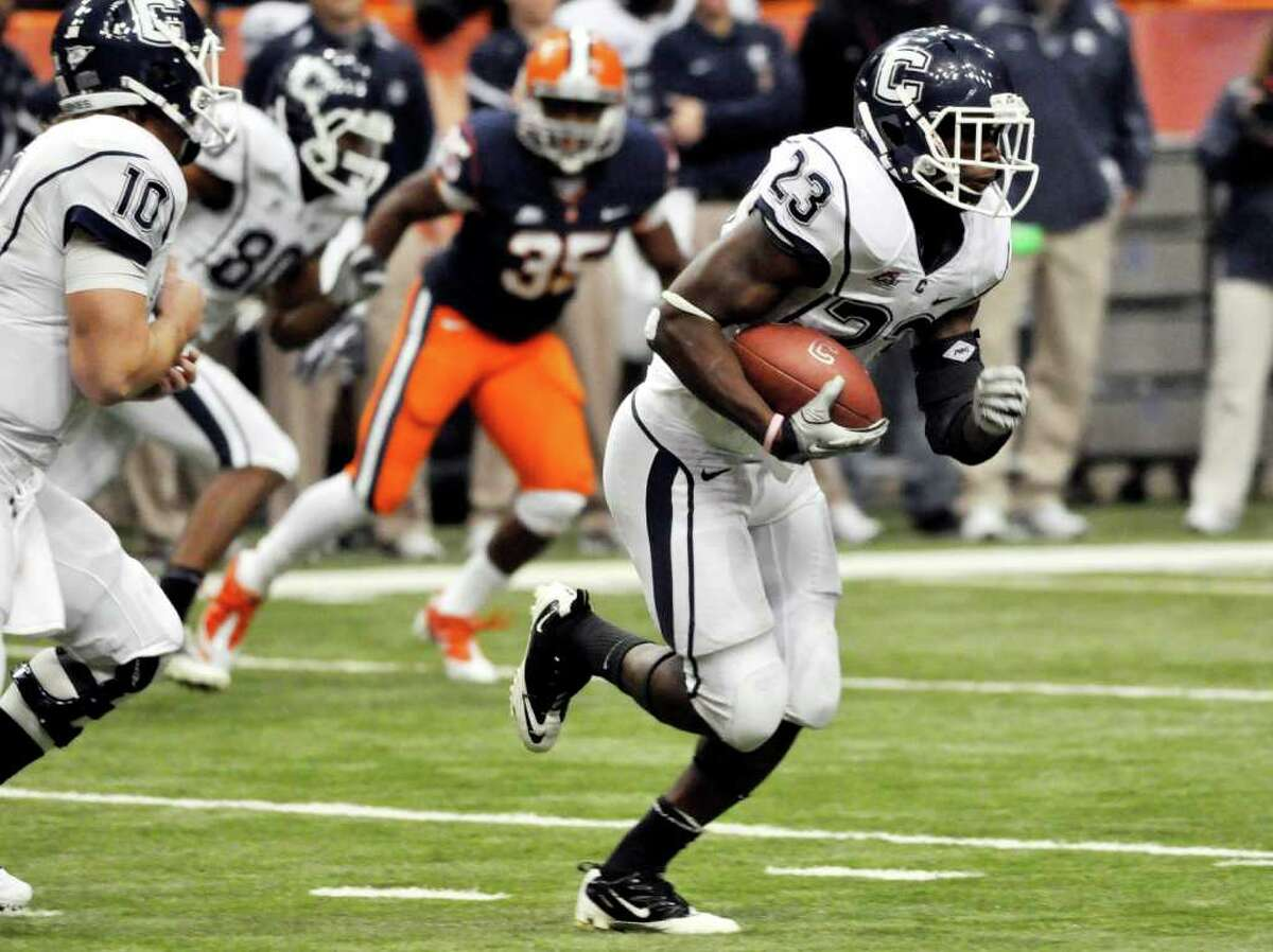 Connecticut's Jordan Todman, right, runs for yardage against Syracuse during the third quarter of an NCAA college football game in Syracuse, N.Y., Saturday, Nov. 20, 2010. Connecticut won 20-6. (AP Photo/Kevin Rivoli)
