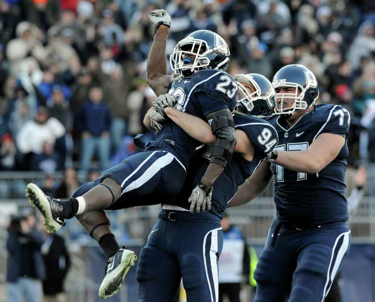 Connecticut's Jordan Todman, left, celebrates a touchdown with teammates Ryan Griffin, center, and Kevin Friend late in the fourth quarter of his team's 38-17 victory over Cincinnati in an NCAA football game in East Hartford, Conn., on Saturday, Nov. 27, 2010. Todman rushed for 175 yards and had three touchdowns in the victory.(AP Photo/Fred Beckham)