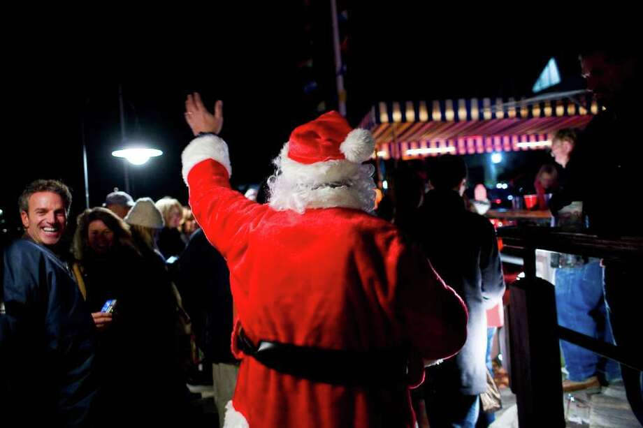 The fifth annual Stamford Harbor Parade of Lights featured numerous boats festooned wth lights cruising through the harbor accompanied by Christmas carols and revelry on the marina's docks. Santa plunges into the crowd outside The Crab Shell. Photo: Andrew Sullivan 2033538537;Andrew Sullivan, Andrew Sullivan / Stamford Advocate Freelance