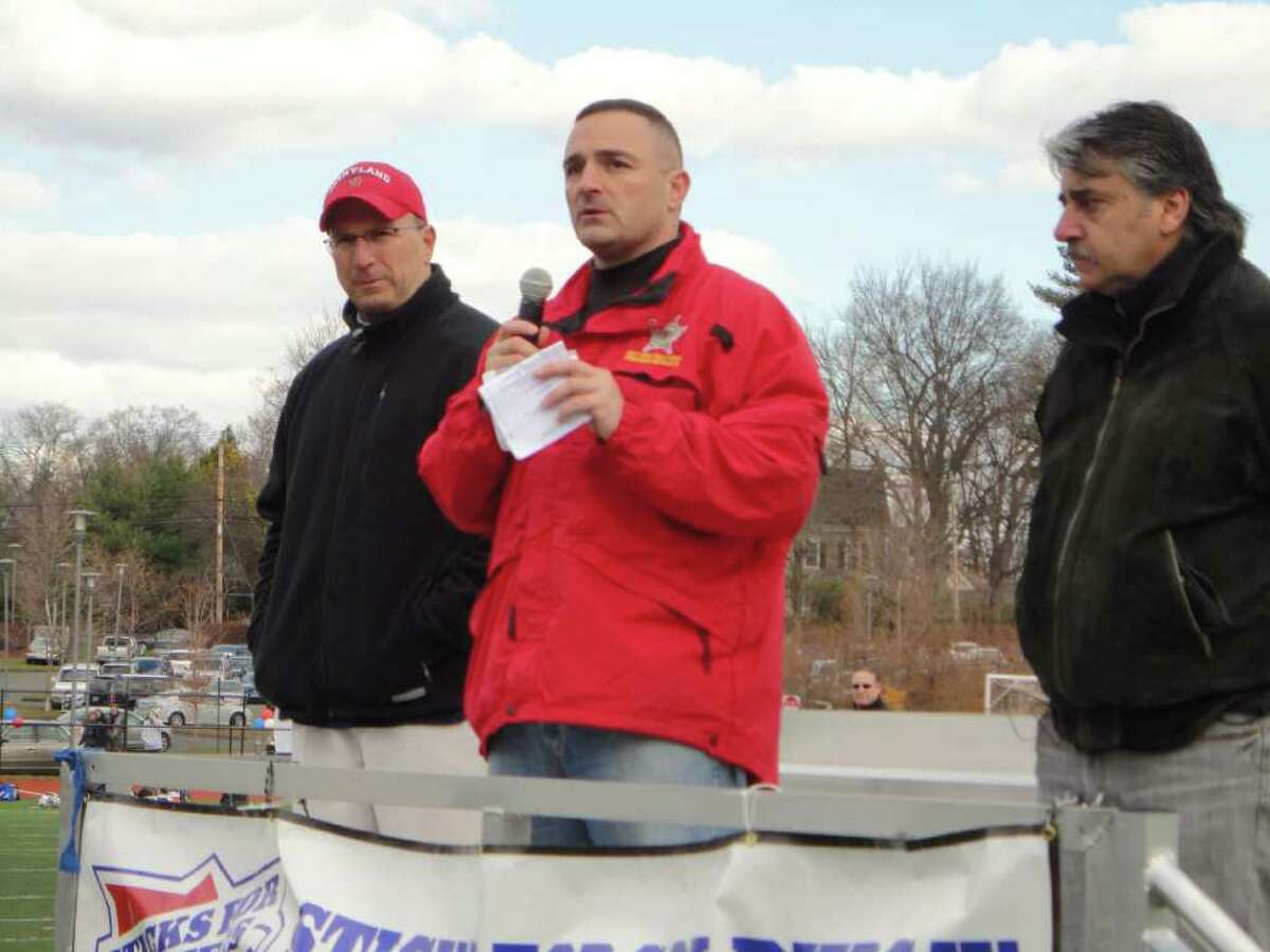 Lt. Col. Tom Armas of Fairfield, a member of the 25th Marine Reserves Regiment at Fort Devens in Massachusetts, on Saturday addresses hundreds of lacrosse players from across the state, thanking them for their efforts to raise money for a wounded soldier in the 5th annual Sticks for Soldiers event in Fairfield. Armas is flanked by Alex Marrocco, right, father of the injured soldier who benefited from the tourneyt, and Mike Voucas, the founder and chairman of Sticks for Soldiers.