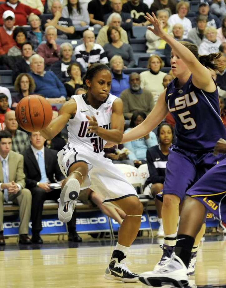 Connecticut's Lorin Dixon brings the ball in as LSU's Jeanne Kenney comes over to block her in the second half of an NCAA women's  basketball game at Storrs, Conn., Sunday, Nov. 28, 2010. Connecticut defeated LSU 81-51.  (AP Photo/Bob Child) Photo: Bob Child, AP / FRE 170410 AP