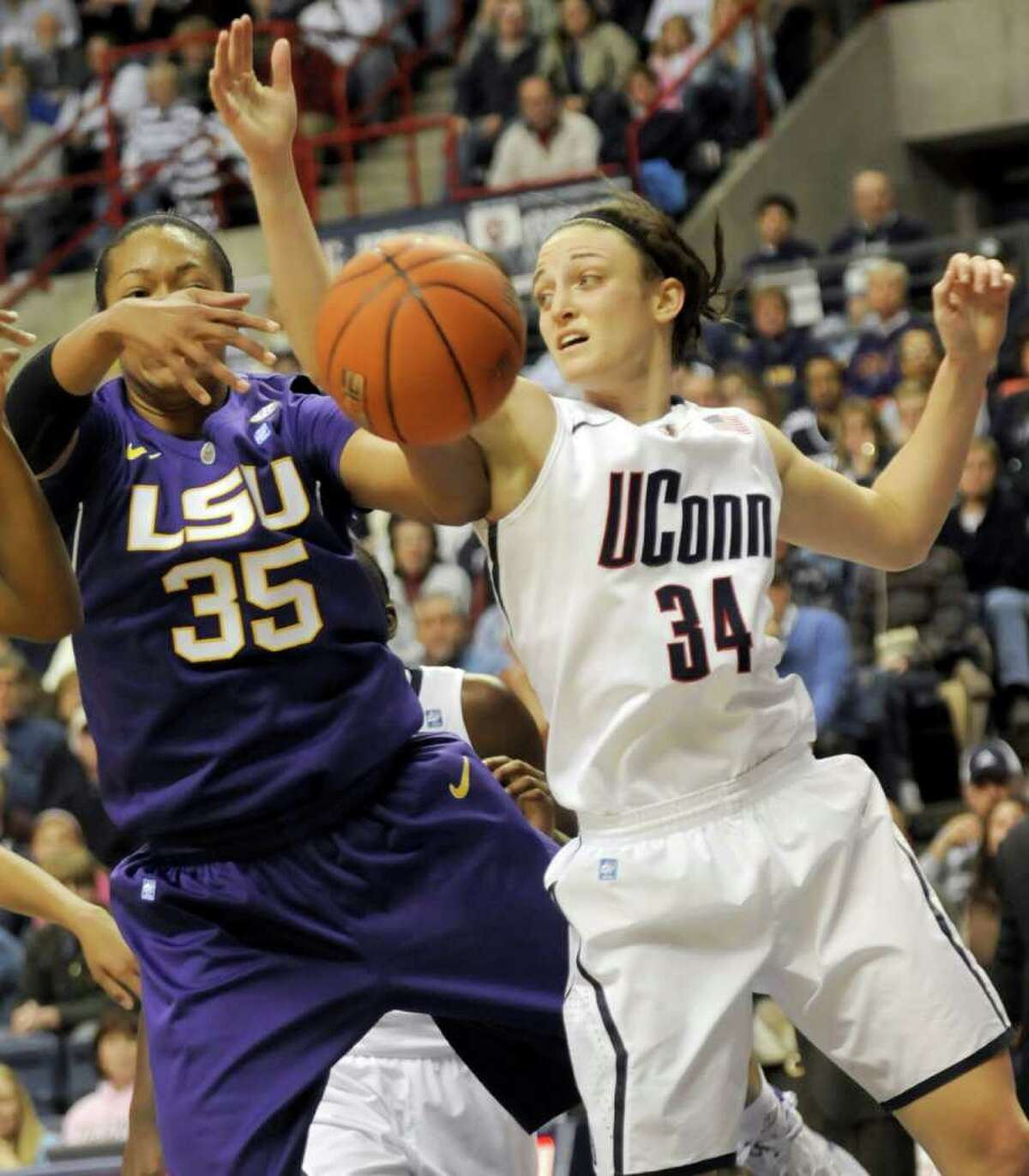 Taylor Turnbow, left, of LSU and Connecticut's Kelly Faris battle for a loose ball in the first half of their NCAA women's basketball game at Storrs, Conn., Sunday, Nov. 28, 2010. (AP Photo/Bob Child)
