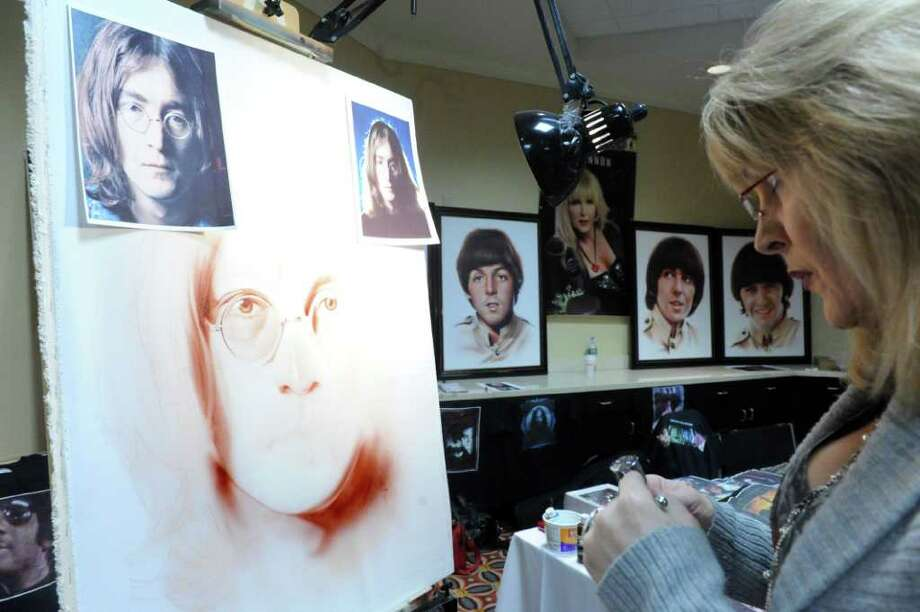 "Shannon MacDonald paints a portrait of John Lennon during ""BEATexpo 2010,"" a convention for Beatles fans at the Holiday Inn Downtown Stamford Sunday, November 28, 2010. MacDonald works with an airbrush and acrylic paints to create her images, in 1998 the Lord Mayor of Liverpool named her the World's Greatest Beatles Artist. The event, which featured booths with collectors items and various memorabilia as well as guest speakers, drew throngs of Beatle fanatics. Photo: Keelin Daly / Greenwich Time"