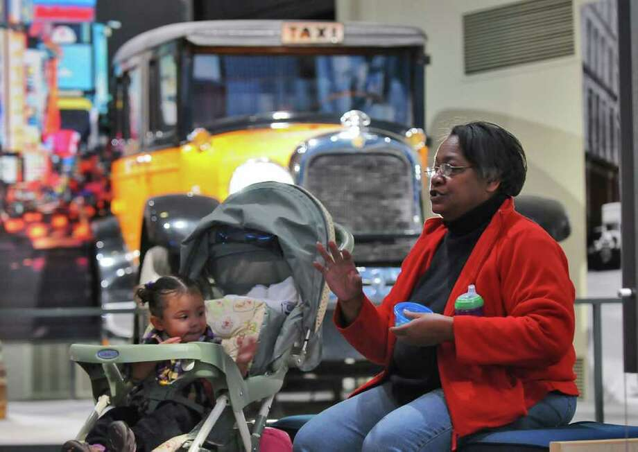 Mary Boston of Niskayuna sits with her granddaughter Kaylee-Angel Moody-Brabham of Albany, 1, during a visit to the New York State Museum in Albany, NY on  Sunday November 28, 2010. Behind them is a taxicab from 1929 that was used in New York City until the mid-1930's. Mary is upset about plans to close the museum on Sundays.  ( Philip Kamrass / Times Uni Photo: Philip Kamrass
