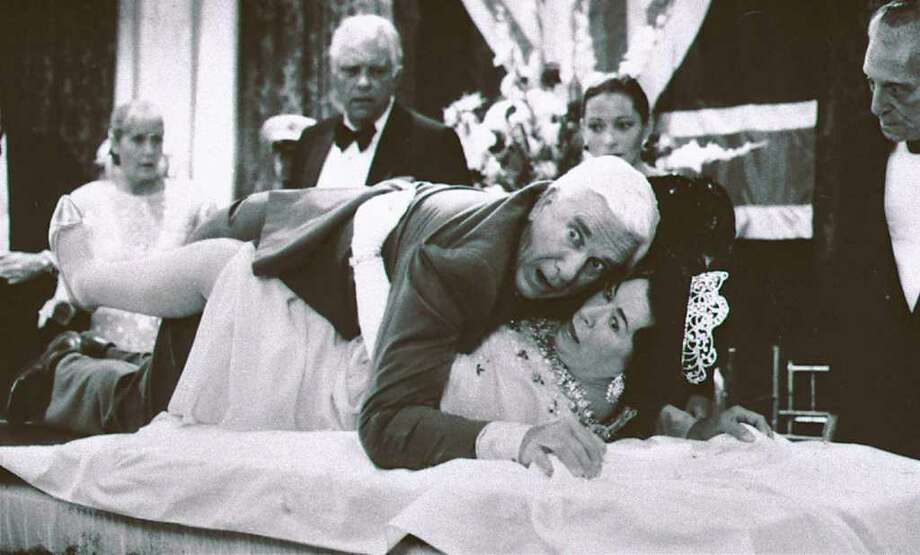 """This 1988 publicity file photo provided by Paramount Pictures shows actor Leslie Nielsen, center top, with actress Jeannette Charles,  portraying the Queen of England, in a scene from """"The Naked Gun."""" The Associated Press/Paramount Pictures, Elliott Marks Photo: Elliott Marks"""