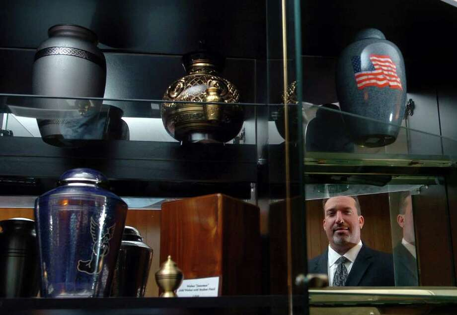 Scott DeMarco, president of All State Cremation and Funeral Care, poses with some of the cremation urns on display for sale at his business on Washington Avenue in Seymour, Conn. on Tuesday November 23, 2010. Photo: Christian Abraham / Connecticut Post