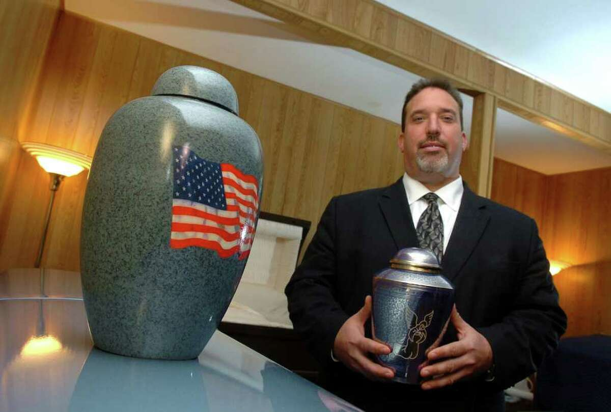 Scott DeMarco, president of All State Cremation and Funeral Care, poses with some of the cremation urns on display for sale at his business on Washington Avenue in Seymour, Conn. on Tuesday November 23, 2010.