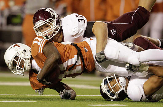 Texas Longhorns wide receiver James Kirkendoll (11) is brought down by Texas A&M Aggies linebacker Michael Hodges (37) and Texas A&M Aggies cornerback Trent Hunter (1) during the first half of the University of Texas-Texans A&M college football game at Texas Memorial Stadium, Nov. 25, 2010, in Ausitn, Texas.