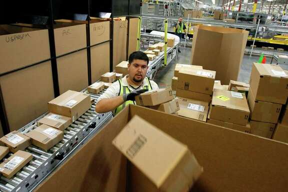 Ricardo Sandoval places packages in the right shipping boxes at an Amazon.com fulfillment center, in Phoenix. (AP Photo/Ross D. Franklin)