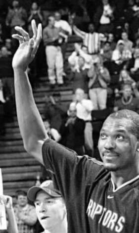 Hakeem Olajuwon, playing for the Raptors, acknowledges the crowd in Houston before a game against the Rockets.