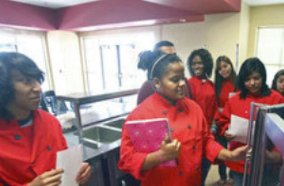Culinary arts student Alexandria Weeding opens doors to an oven in the Southside High School's new career and technology education center.