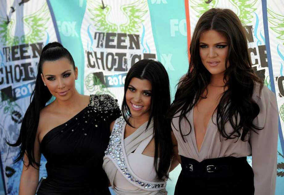 Kim Kardashian, Kourtney Kardashian and Khloe Kardashian arrive at the Teen Choice Awards in Universal City, Calif. The Kardashian sisters are seeking to cut ties with a venture that sold prepaid debit cards under their name after coming under attack for the card's high fees. Chris Pizzello/The Associated Press Photo: Chris Pizzello, STF / AP