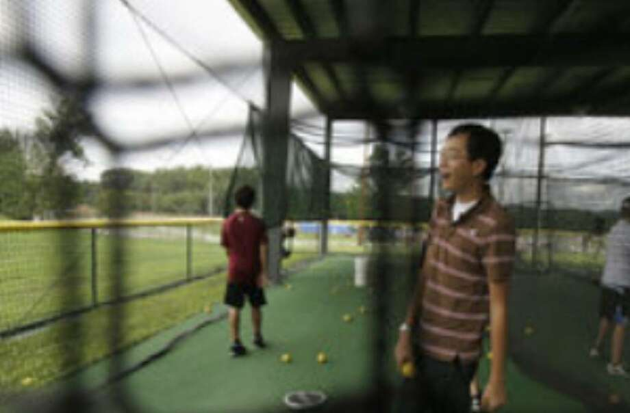 Express-News reporter Lorne Chan watches the McAllister Park Little Leaguers' batting practice Thursday in South Williamsport, Pa. Chan went on to prove his baseball expertise is limited to writing.