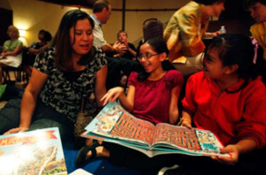 """Sierra Gonzales, 10, and Yesenia Rodriguez, 9, (right) look to Mary Rodriguez, their assistant principal at Madison Elementary, as they try to find a list of objects in a drawing from Roxie Munro's """"Rodeo."""" The fourth-graders got the field trip as a reward for good schoolwork."""