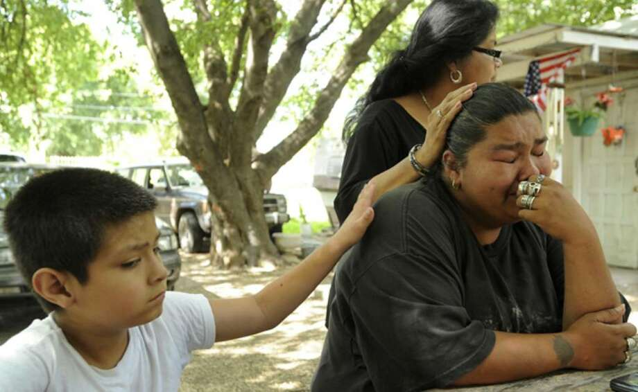 Georgette Sifuentes is comforted by son Oliver and her mother, Yolanda Sifuentes. Her husband, Juan Duran, died after being beaten during a road-rage incident on the West Side.