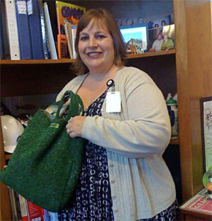 Lisa McKenzie, head of San Antonio's graffiti abatement program, sports her grass purse made of Astroturf.