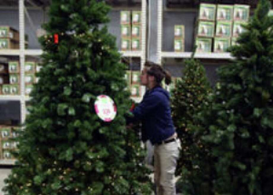 Walmart's Tabatha Bielefeld puts lights on an artificial Christmas tree at the store. A National Retail Federation forecast of holiday sales expects a 1 percent decline this year.