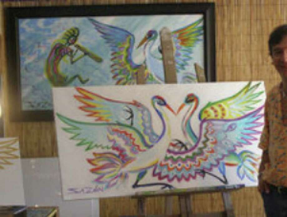 Ruben Sazón's work centers on the whooping crane's folkloric ties to fidelity and current struggle for survival. The hanging painting on the left includes the fertility god Kokopelli.