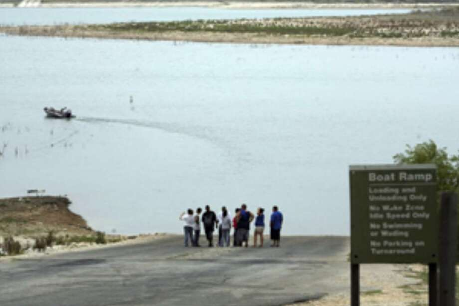 People stand on a boat ramp Monday at Canyon Lake as law enforcement continues a search for 20-year-old woman that fell off a boat Sunday night.