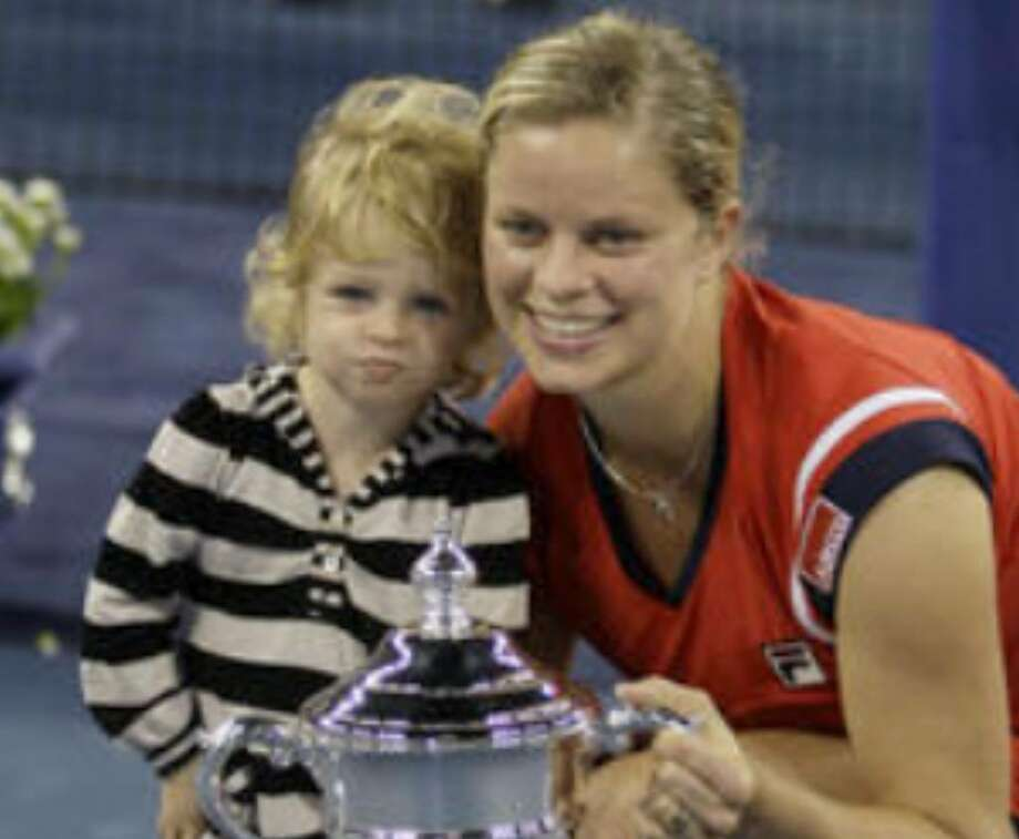 Kim Clijsters poses with her daughter, Jada, and the championship trophy after winning the women's final against Caroline Wozniacki at the U.S. Open. Clijsters became the first unseeded woman to win the tournament.