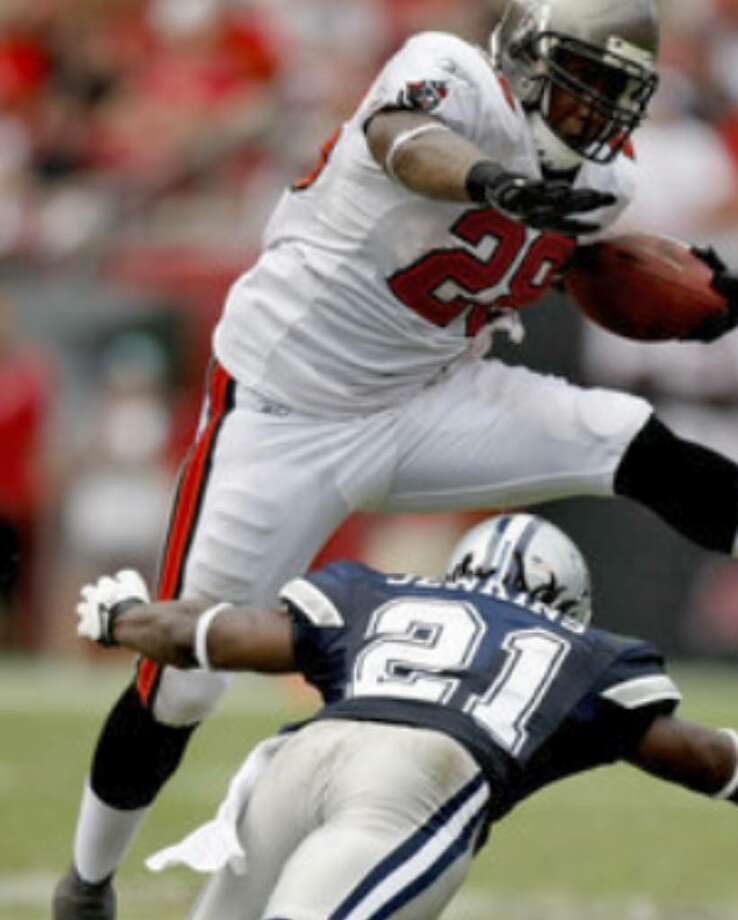 Buccaneers running back Derrick Ward (28) hurdles Mike Jenkins during the third quarter of the Cowboys' season-opening victory.