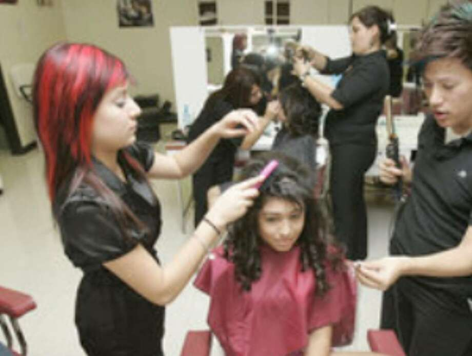 Lithbeth Banda (left), 17, and Rudy Urbina, 19, both seniors in the Fox Tech High School cosmetology program, style Genevieve Jimenez's hair for the Quinceañera Fashion Show. Jimenez, 14, is a ninth-grader at Judson High.