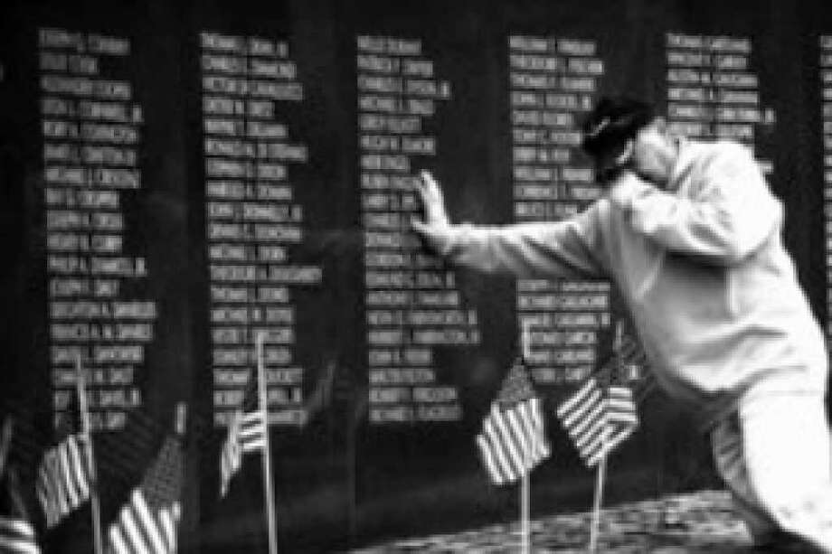 Veteran Mario Morrone of Philadelphia pays his respects to friends who died while serving in Vietnam, at the Vietnam Veterans Memorial on Veterans Day in Philadelphia.