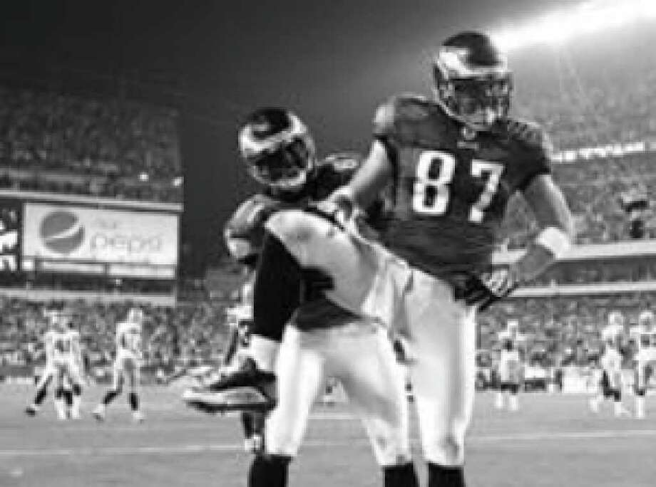 Eagles tight end Brent Celek (87) strikes the Captain Morgan rum pose after scoring against Dallas last Sunday. Jason Avant assisted in the celebration, which cost Philadelphia a 15-yard penalty.