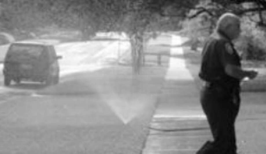 A SAWS water enforcer walks past a sprinkler at a home in the Monte Vista area.