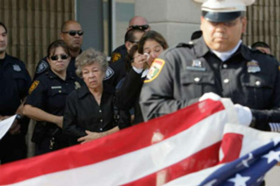 San Antonio Police Department central substation officers fold a U.S. flag to give to the family of the late Sgt. Alfred Trinidad. He died Tuesday.