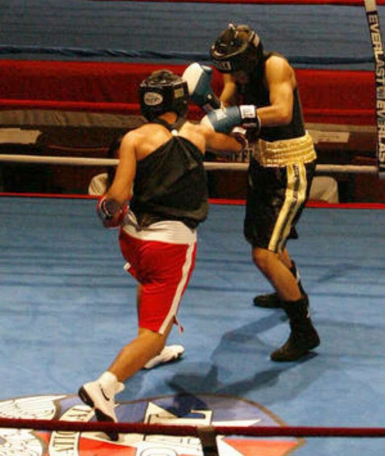 Boxers square off in two of the three rings during the opening day of National Police Athletic League Championships at Municipal Auditorium. The tournament runs through Saturday.