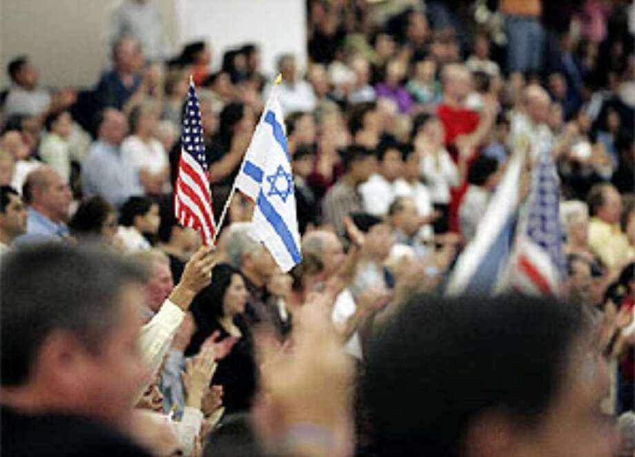 """Attendees wave the flags of the United States and Israel during """"A Night to Honor Israel,"""" a yearly event to promote solidarity between Christians and Jews at Cornerstone Church."""