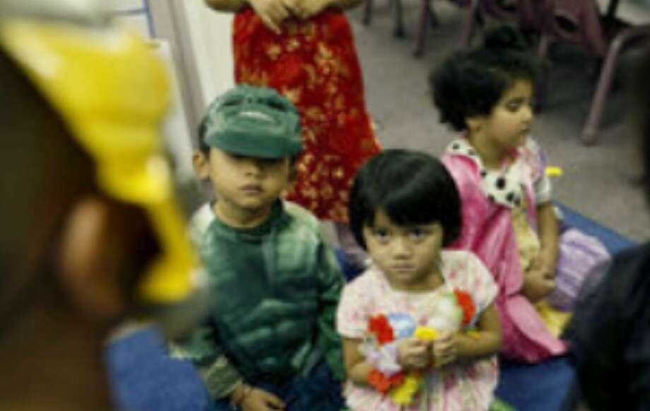 Soe Reh (from left) and A Lee Naw, both refugees from Myanmar (Burma), and Sura Ali, a refugee from Iraq, watch as other schoolchildren walk through their classroom collecting candy during the Culebra Head Start's fall festival.