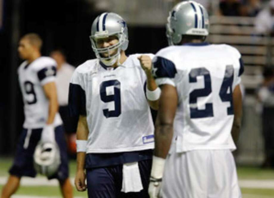Tony Romo offers a fist bump to Roy Williams during camp. They have connected six times this preseason.