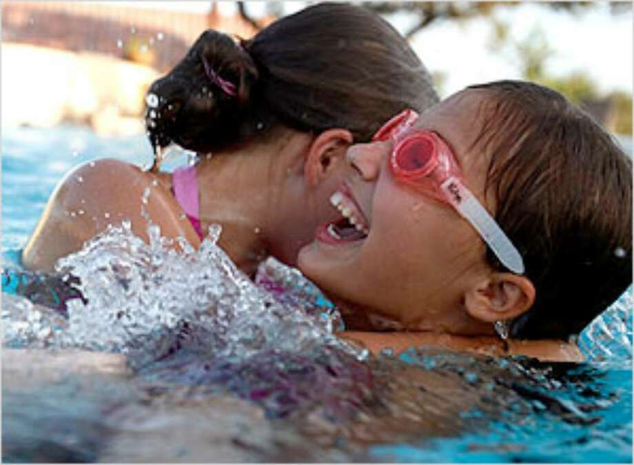 Galina, 11 (right), and Vika, 13, play in the pool with other Ukrainian orphans and their host families.